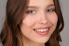 Adolescente con crema en su cara Cierre para arriba Fondo gris Imagen de archivo libre de regalías