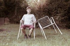 Adolescente con dos sillas Fotos de archivo