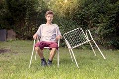Adolescente con dos sillas Imagen de archivo