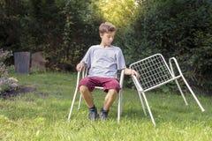 Adolescente con dos sillas Fotos de archivo libres de regalías