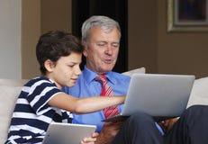 Adolescente con el abuelo en casa Foto de archivo libre de regalías