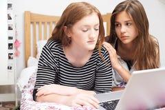 Adolescente con el amigo que es tiranizado en línea Fotos de archivo libres de regalías