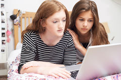 Adolescente con el amigo que es tiranizado en línea Foto de archivo