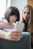 Adolescente con el amigo que es tiranizado por el mensaje de texto Foto de archivo