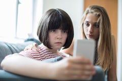 Adolescente con el amigo que es tiranizado por el mensaje de texto Fotografía de archivo