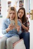 Adolescente con el amigo que es tiranizado por el mensaje de texto Imagenes de archivo