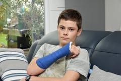 Adolescente con el brazo derecho en yeso Imagenes de archivo