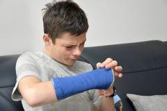 Adolescente con el brazo derecho en yeso Fotos de archivo
