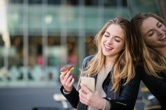 Adolescente con el buñuelo y el móvil Imágenes de archivo libres de regalías