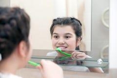 Adolescente con el cepillo de dientes en baño Foto de archivo libre de regalías
