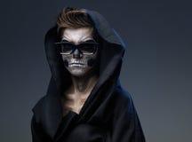 Adolescente con el cráneo del maquillaje en vidrios negros del cabo Imagenes de archivo