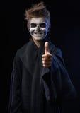 Adolescente con el cráneo del maquillaje que muestra los pulgares para arriba Fotografía de archivo libre de regalías