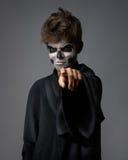 Adolescente con el cráneo del maquillaje señala el finger Fotografía de archivo