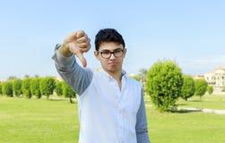 Adolescente con el desgaste del ojo que muestra sus pulgares abajo Fotos de archivo