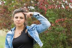 Adolescente con el finger que señala en su cabeza Imagen de archivo libre de regalías