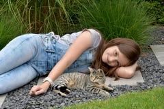 Adolescente con el gato de gato atigrado Fotos de archivo libres de regalías