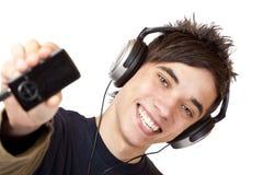 Adolescente con el jugador de música del mp3 de las demostraciones de los auriculares Foto de archivo libre de regalías