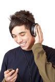 Adolescente con el jugador de música del mp3 del uso del receptor de cabeza Fotos de archivo