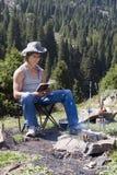 Adolescente con el libro en alza de la montaña Imagen de archivo
