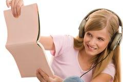 Adolescente con el libro que escucha la música Fotografía de archivo