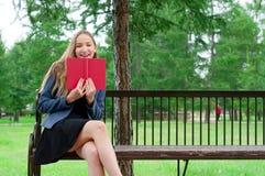 Adolescente con el libro rojo en banco en parque de la ciudad Imágenes de archivo libres de regalías