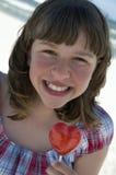 Adolescente con el lollipop en la playa Imagen de archivo libre de regalías