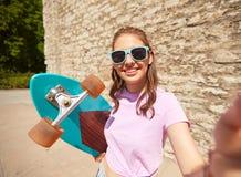 Adolescente con el longboard que toma el selfie al aire libre Foto de archivo