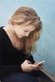 Adolescente con el móvil que toma un selfie o una escritura SMS Imagenes de archivo