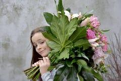 Adolescente con el manojo de flores grande Imagen de archivo libre de regalías