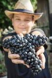 Adolescente con el manojo de uvas en manos, tema del vintage Fotos de archivo