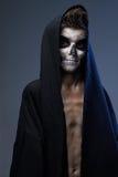 Adolescente con el maquillaje del cráneo en cabo negro Foto de archivo