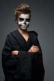 Adolescente con el maquillaje del cráneo en cabo negro Imágenes de archivo libres de regalías