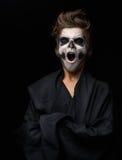 Adolescente con el maquillaje del cráneo en cabo negro bosteza Foto de archivo libre de regalías
