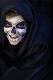 Adolescente con el maquillaje del cráneo en capa negra ríe Imágenes de archivo libres de regalías