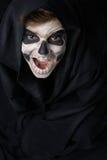 Adolescente con el maquillaje del cráneo en capa negra ríe Imagenes de archivo