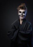 Adolescente con el maquillaje del cráneo en capa negra ríe Fotos de archivo libres de regalías