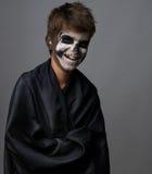 Adolescente con el maquillaje del cráneo en capa negra ríe Fotos de archivo