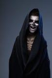 Adolescente con el maquillaje del cráneo en capa negra ríe Fotografía de archivo