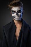 Adolescente con el maquillaje del cráneo en la capa negra infeliz Foto de archivo libre de regalías