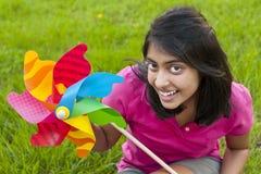 Adolescente con el molinillo de viento Fotos de archivo