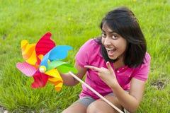 Adolescente con el molinillo de viento Foto de archivo libre de regalías
