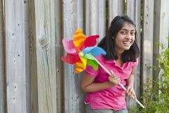 Adolescente con el molinillo de viento Imagen de archivo