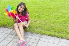 Adolescente con el molinillo de viento Fotografía de archivo