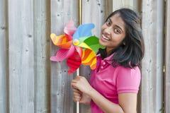 Adolescente con el molinillo de viento Imagenes de archivo