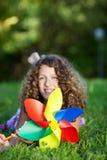 Adolescente con el molinillo de viento que miente en hierba Fotos de archivo
