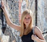 Adolescente con el monedero contra la pared de la pintada Foto de archivo libre de regalías