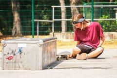 Adolescente con el monopatín Imagen de archivo