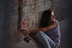 Adolescente con el monopatín en la calle Foto de archivo