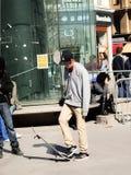 Adolescente con el monopatín en la calle Imagenes de archivo