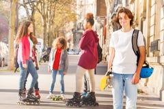 Adolescente con el monopatín en la calle de la ciudad Fotos de archivo